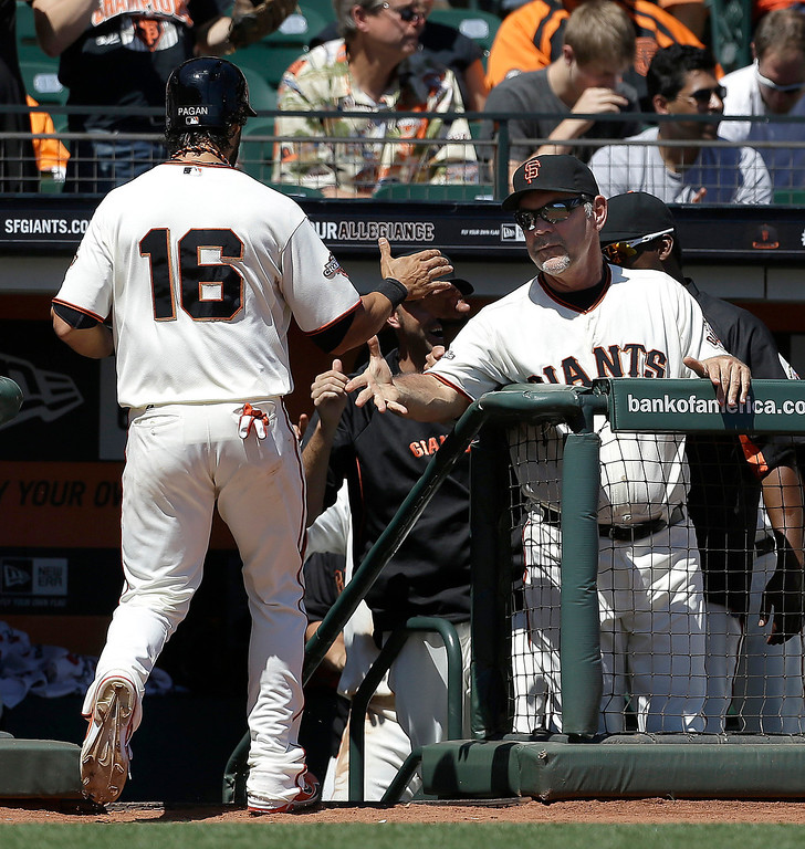 . San Francisco Giants\' Angel Pagan (16) is congratulated by manager Bruce Bochy, right, after scoring during the second inning of a baseball game against the Colorado Rockies in San Francisco, Wednesday, April 10, 2013. (AP Photo/Jeff Chiu)