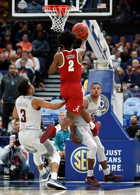 . Alabama\'s Collin Sexton (2) makes a basket at the buzzer as Texas A&M\'s Admon Gilder (3) and Savion Flagg watch during the second half in an NCAA college basketball game at the Southeastern Conference tournament Thursday, March 8, 2018, in St. Louis. Alabama won 71-70. (AP Photo/Jeff Roberson)