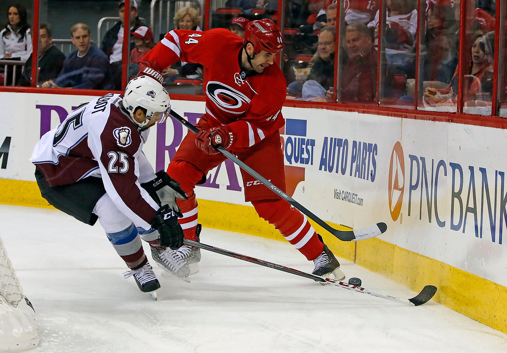 . Colorado Avalanche\'s Maxime Talbot (25) and Carolina Hurricanes\' Jay Harrison (44) battle for the puck during the first period of an NHL hockey game in Raleigh, N.C., Tuesday, Nov. 12, 2013. (AP Photo/Karl B DeBlaker)