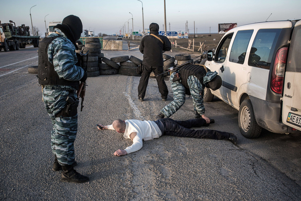 . Pro-Russian servicemen search a man at Chongar checkpoint blocking the entrance to Crimea on March 10, 2014. Russia vowed on March 10 to unveil its own solution to the Ukrainian crisis that would run counter to US efforts and would appear to leave room for Crimea to switch over to Kremlin rule. The unexpected announcement came as Ukraine\'s new pro-European leaders raced to rally Western support in the face of the seizure by Kremlin-backed forces of the strategic Black Sea peninsula and plans to hold a Sunday referendum on switching Crimea\'s allegiance from Kiev to Moscow. AFP PHOTO/ ALISA BOROVIKOVAALISA BOROVIKOVA/AFP/Getty Images