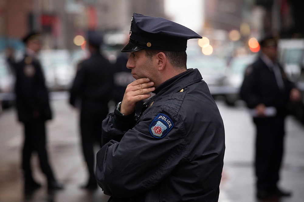 Description of . A police officer stands at the site of a shooting near Columbus Circle in Manhattan, New York December 10, 2012. New York City police are looking for a suspect after a person was shot in the head in Manhattan, local media reported.  REUTERS/Adrees Latif