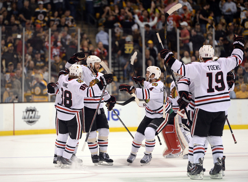 . Brent Seabrook #7 of the Chicago Blackhawks celebrates with Patrick Kane #88, Niklas Hjalmarsson #4 and Jonathan Toews #19 after scoring the game winning goal in overtime against the Boston Bruins in Game Four of the 2013 NHL Stanley Cup Final at TD Garden on June 19, 2013 in Boston, Massachusetts.  (Photo by Harry How/Getty Images)