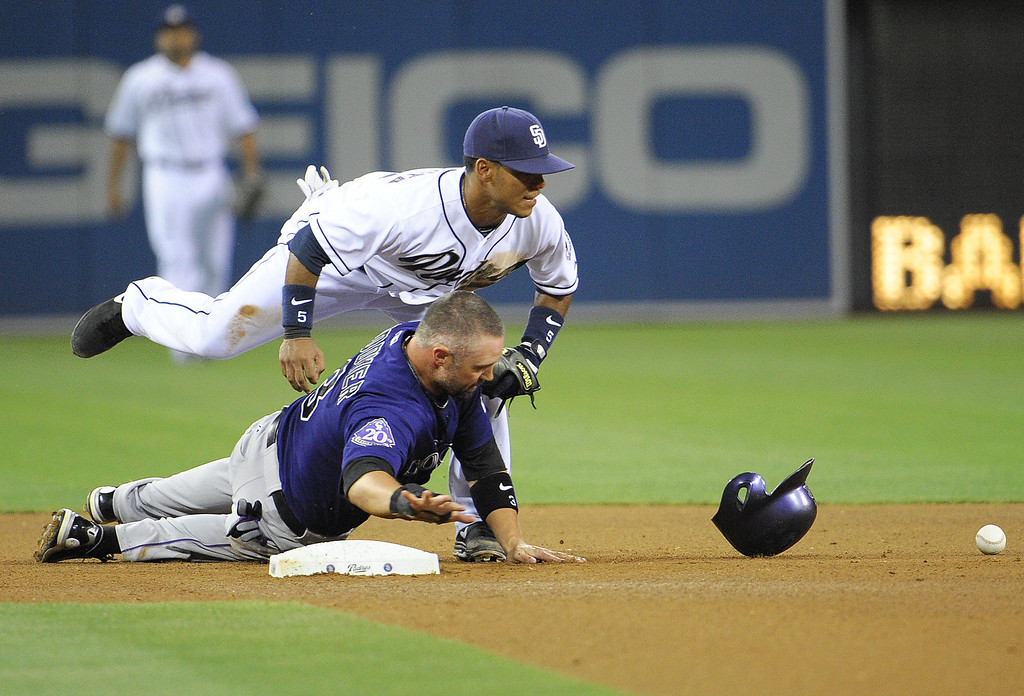 . Alexi Amarista #5 of the San Diego Padres drops the ball after colliding with Michael Cuddyer #3 of the Colorado Rockies while trying to turn a double play during the fourth inning of a baseball game at Petco Park on July 9, 2013 in San Diego, California.  (Photo by Denis Poroy/Getty Images)