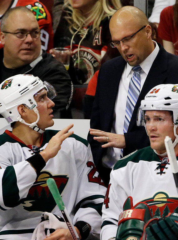 . Minnesota Wild head coach Mike Yeo talks to Nino Niederreiter (22) as Matt Cooke (24) looks to the ice during the first period. (AP Photo/Nam Y. Huh)