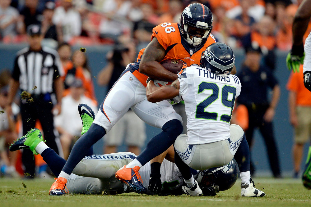 . Wide receiver Demaryius Thomas (88) of the Denver Broncos makes a first-down catch as he is tackled by free safety Earl Thomas (29) of the Seattle Seahawks during the first half of action at Sports Authority Field at Mile High. The Denver Broncos hosted the Seattle Seahawks in an NFL preseason game. (Photo by AAron Ontiveroz/The Denver Post)