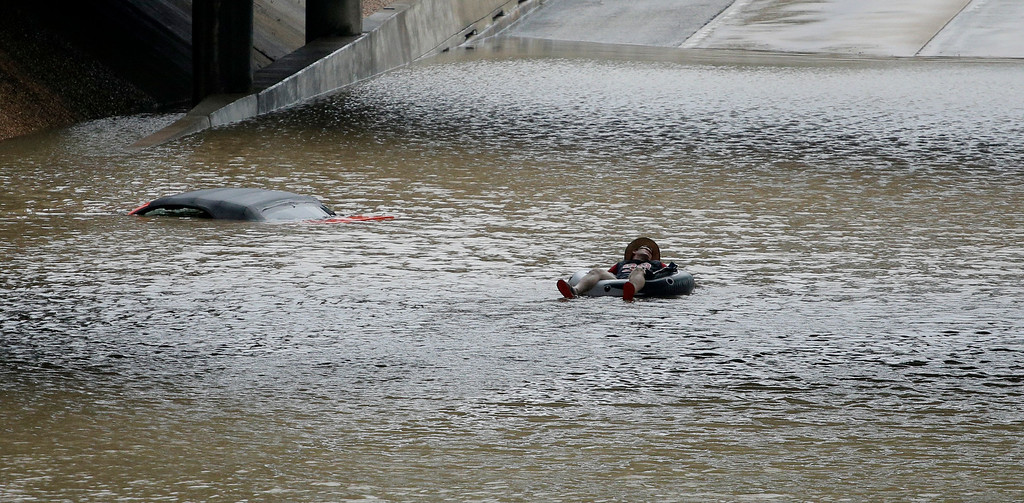 . A man floats past a stalled car submerged on a freeway flooded by Tropical Storm Harvey on Sunday, Aug. 27, 2017, near downtown Houston. The remnants of Hurricane Harvey sent devastating floods pouring into Houston Sunday as rising water chased thousands of people to rooftops or higher ground. (AP Photo/Charlie Riedel)