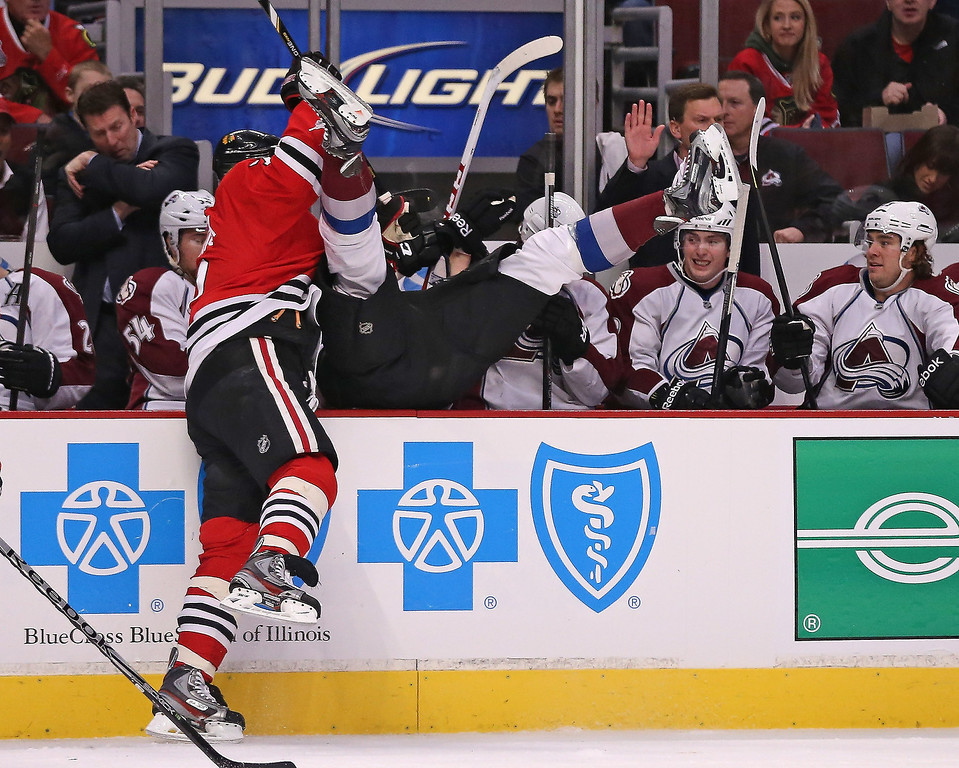 . Brent Seabrook #7 of the Chicago Blackhawks dumps Patrick Bordeleau #58 of the Colorado Avalanche over the boards at the United Center on March 6, 2013 in Chicago, Illinois.  (Photo by Jonathan Daniel/Getty Images)