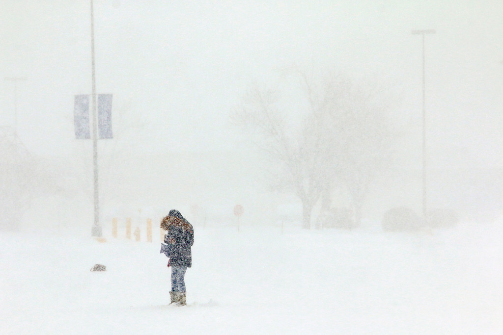 . A pedestrian tries to make it through the snow in the Market Basket parking lot in Leominster on Tuesday afternoon March 14, 2017. SENTIENL & ENTERPRISE/JOHN LOVE