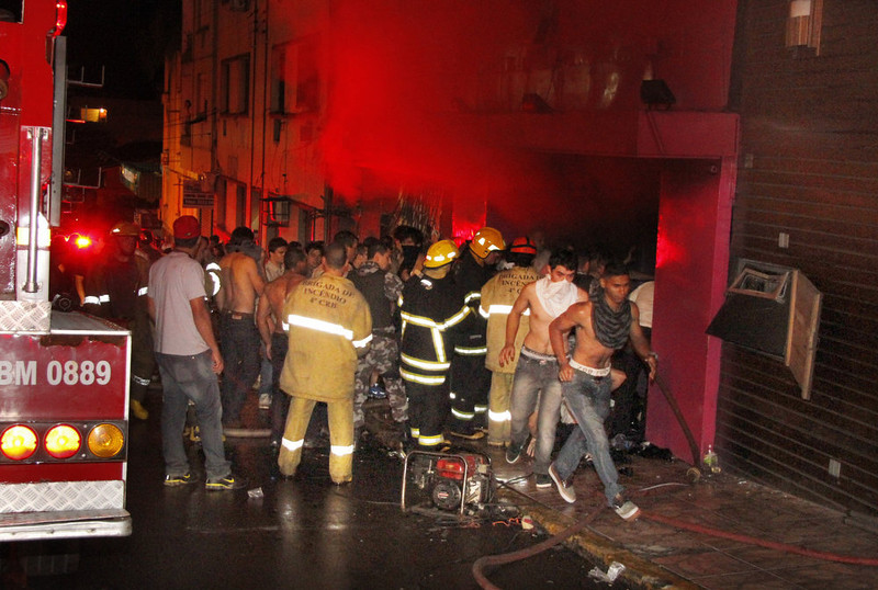. People gather outside the Kiss nightclub as firefighters respond to a fire inside the club in Santa Maria, Brazil, Sunday, Jan. 27, 2013. A fast-moving fire roared through the crowded, windowless Kiss nightclub in this southern Brazilian city early Sunday, killing more than 230 people. Many of the victims were under 20 years old, including some minors. (AP Photo/Deivid Dutra, Agencia Brasil)