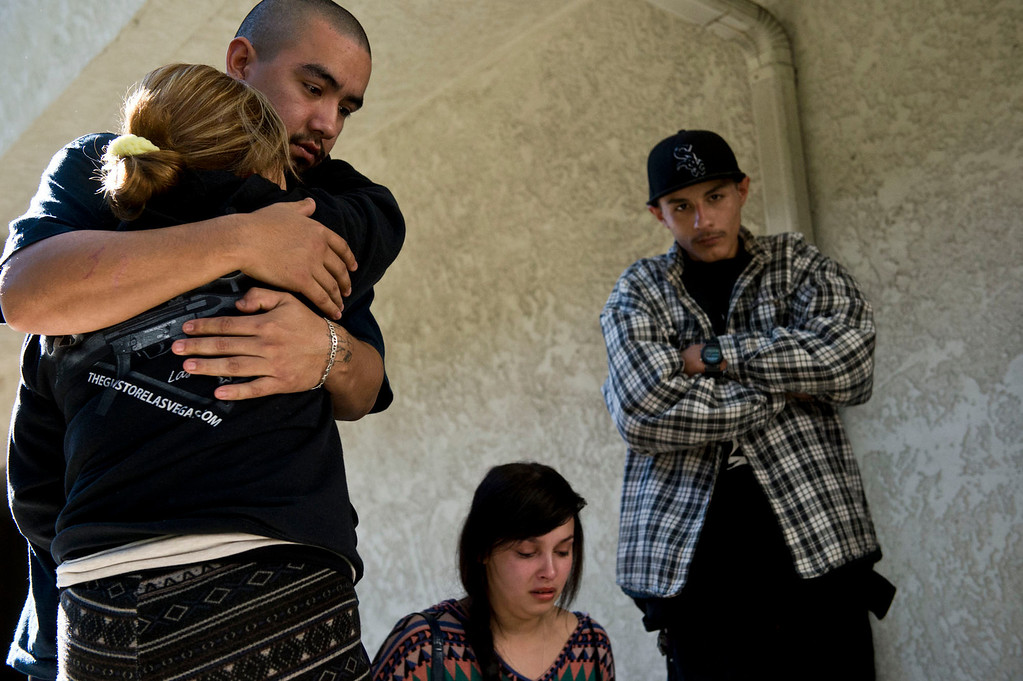 . Carmen Avila, left, is comforted by a family member as she mourns over the death of her son, Cristopher Rossi, 16, as friends and family gathered at the makeshift memorial outside their Duarte apartment on Tuesday, Dec. 24, 2013. Rossi was fatally shot outside his home Monday night. (Staff photo by Watchara Phomicinda/ San Gabriel Valley Tribune)