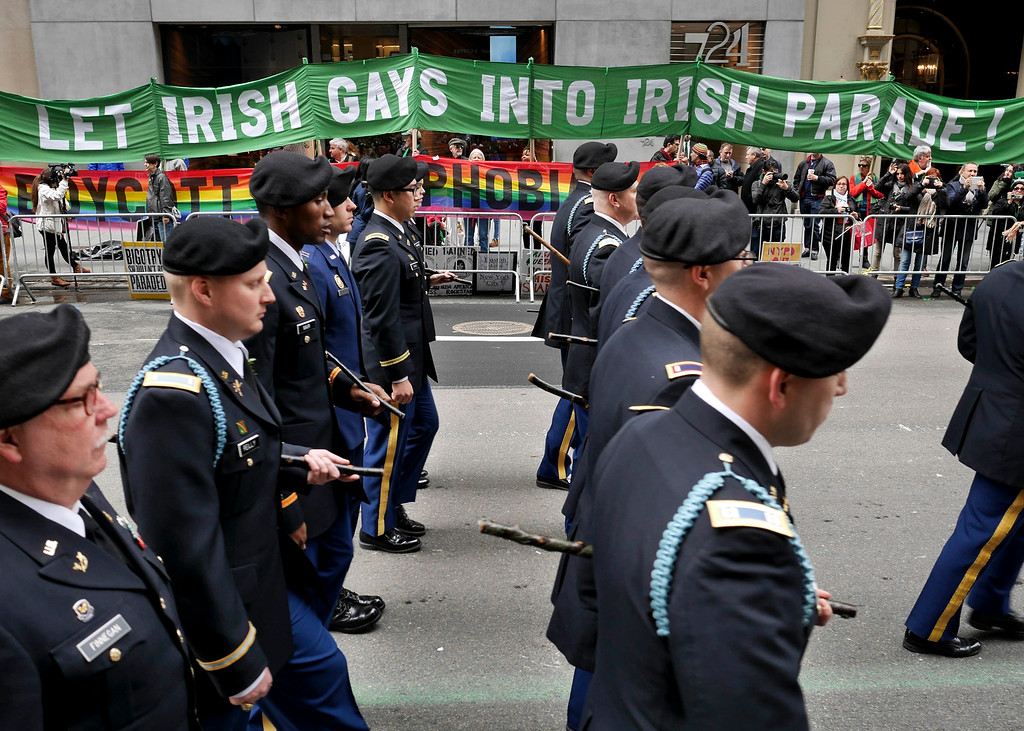 . Marchers walk past a group of protesters during the St. Patrick\'s Day Parade in New York, Tuesday, March 17, 2015. The group was protesting the exclusion of LGBT groups from the parade. (AP Photo/Seth Wenig)