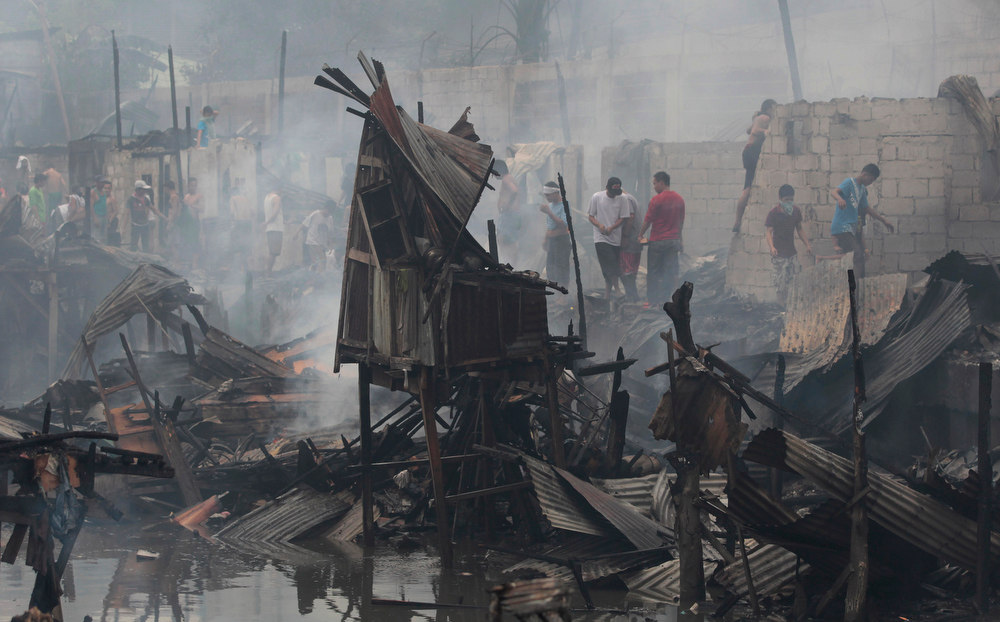 . Residents return to their still smoldering homes after a fire broke out at a slum area in Pasay, south of Manila, Philippines on Wednesday, July 24, 2013. Pasay City Fire Marshall Major Douglas Guiyab said about 250 houses were gutted in the area and the cause of the fire is still being determined. (AP Photo/Aaron Favila)