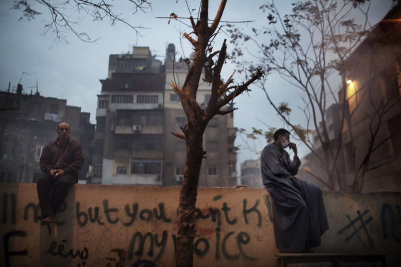 ". Egyptian demonstrators sit on a graffiti-covered wall during a lull in confrontations with riot police on February 6, 2012 outside Cairo\'s security headquarters. The United States must ""re-evaluate\"" its ties with Egypt in response to  Egypt\'s apparent plans to put dozens of pro-democracy activists, including 19 Americans, on trial, according to a US senator.  MARCO LONGARI/AFP/Getty Images"