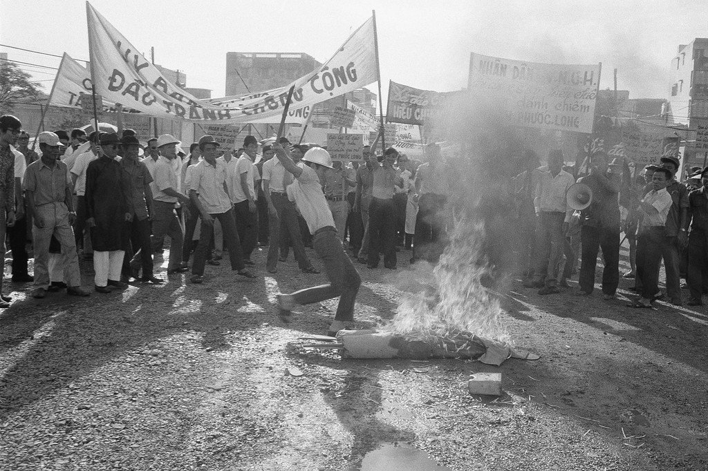 . Anticommunist demonstrator kicks burning effigy of Viet Cong soldier during unruly protest outside Saigon headquarters of International Commission of Control and Supervision in Saigon, Jan. 6, 1975. About a hundred demonstrators protested fierce fighting in Phuoc Long province in violation of the Paris peace agreement, which the ICCS is charged with enforcing. (AP Photo)