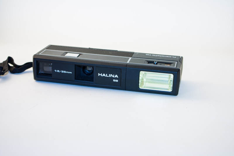 Halina Sharpshooter Flashmatic This is a 110 cartridge film camera which has a built-in flash, powered by two AA batteries.