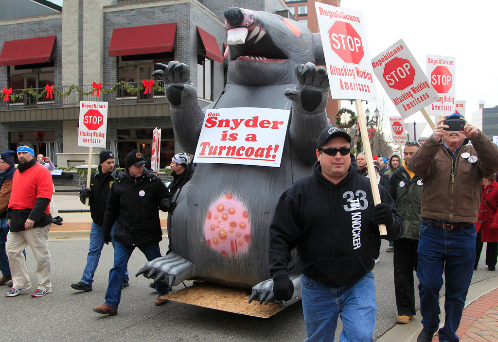 . Sheet metal workers from Toledo escort an inflatable rat during a march to the State Capitol grounds in Lansing, Mich., Tuesday, Dec. 11, 2012. The crowd is protesting right-to-work legislation that was passed by the state legislature last week. (AP Photo/Carlos Osorio)
