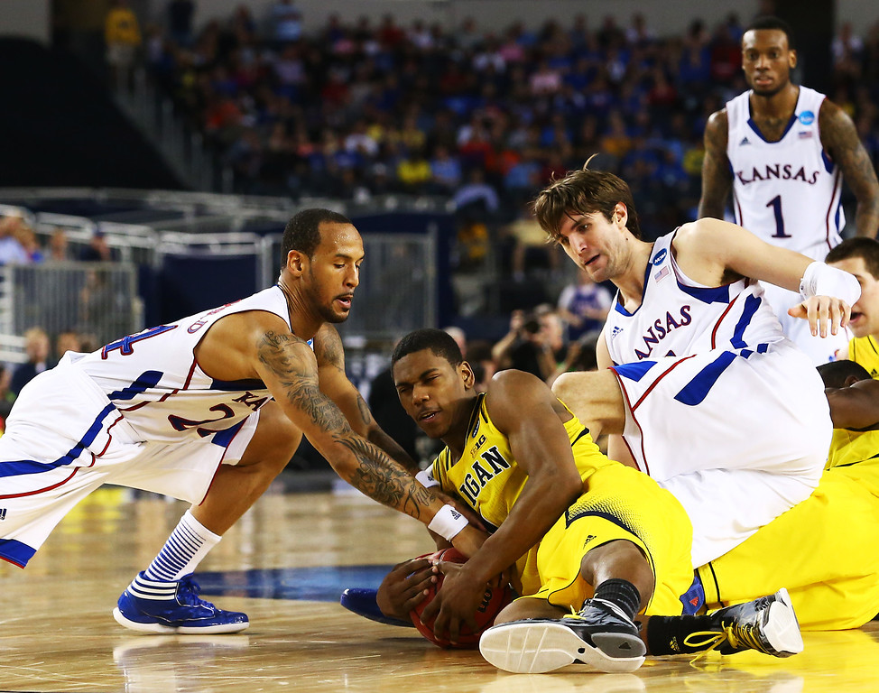 . ARLINGTON, TX - MARCH 29:  Trey Burke #3 of the Michigan Wolverines vies for a loose ball with Jeff Withey #5 and Travis Releford #24 of the Kansas Jayhawks in the second half during the South Regional Semifinal round of the 2013 NCAA Men\'s Basketball Tournament at Dallas Cowboys Stadium on March 29, 2013 in Arlington, Texas.  (Photo by Ronald Martinez/Getty Images)