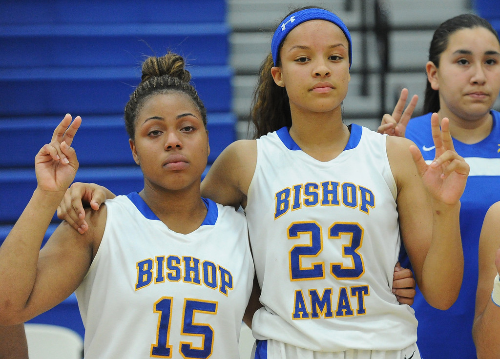 . Bishop Amat\'s Leeah Powell (15) along with teammate Mauriana Clayton (23) sings the alma mater after Long Beach Poly won 52-34  during a CIF State Southern California Regional semifinal basketball game at Bishop Amat High School on Tuesday, March 12, 2013 in La Puente, Calif.  (Keith Birmingham Pasadena Star-News)