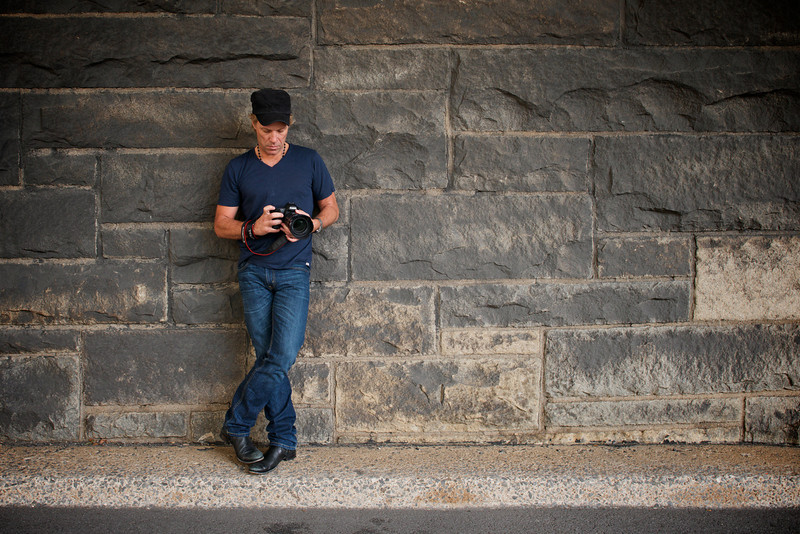 ". September 26, 2012 - Jon Bon Jovi checks the settings on his camera during a photo lesson in New York, NY on September 26, 2012.  (Photo credit: David Bergman / Bon Jovi)  ""Jon Bon Jovi is a smart guy who loves to learn new things,\"" says Bergman. \""As a creative person, he�s always been interested in photography and, after watching me work day after day photographing him, he starting asking questions. I occasionally teach individual and group photo workshops, but he�s clearly my highest profile photo student! During the tour on non-show days, we would walk around parks in the neighborhood and I�d teach him about apertures and shutter speeds. He�s got a great eye, but didn�t know the technical aspects of making an image. I took this photo of him in lower Manhattan, New York City, as he adjusted the settings on his camera. Inside WORK, there�s a special section featuring some of the images he�s taken on family vacations around the world and I�m quite proud of his work! It�s quite a unique look at Jon�s life literally through his own eyes.\"""