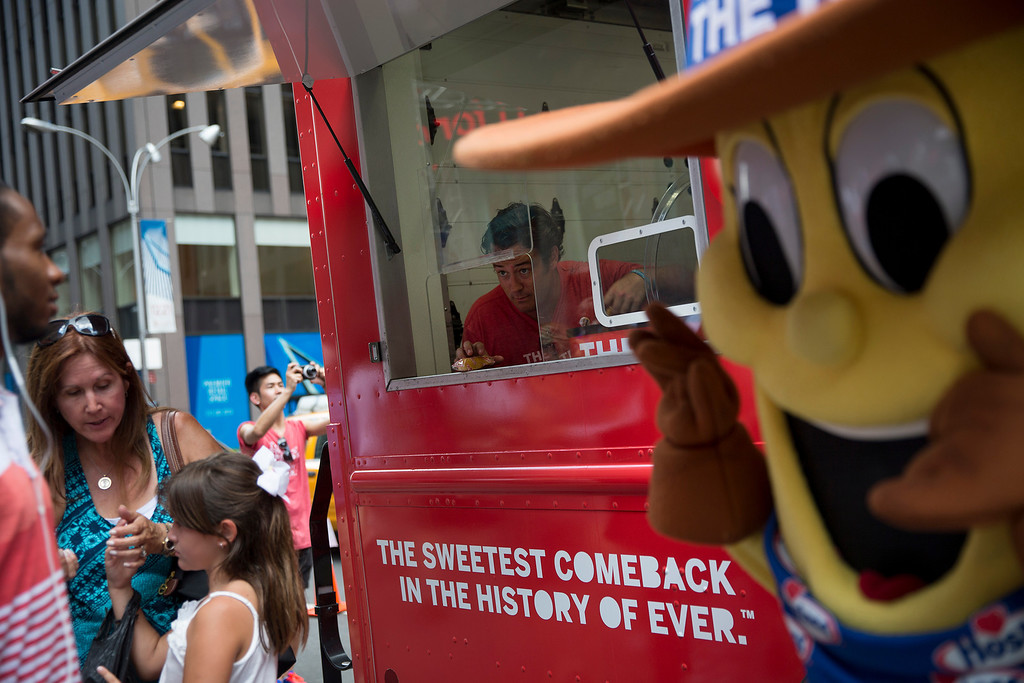 . Chad Reinhart hands out Hostess Brands LLC Twinkies snack cakes to passersby as part of a promotion in New York, U.S., on Monday, July 15, 2013. Photographer: Scott Eells/Bloomberg
