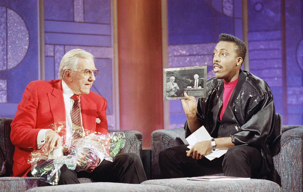 ". Ed McMahon, left, long time side-kick of talk show host Johnny Carson, presents a coffee mug to talk show host Arsenio Hall as Hall shows a picture of McMahon and Carson from ""The Tonight Show With Johnny Carson\"" during the taping of \""The Arsenio Hall Show,\"" June 1, 1992 in Los Angeles. (AP Photo/Kevork Djansezian)"