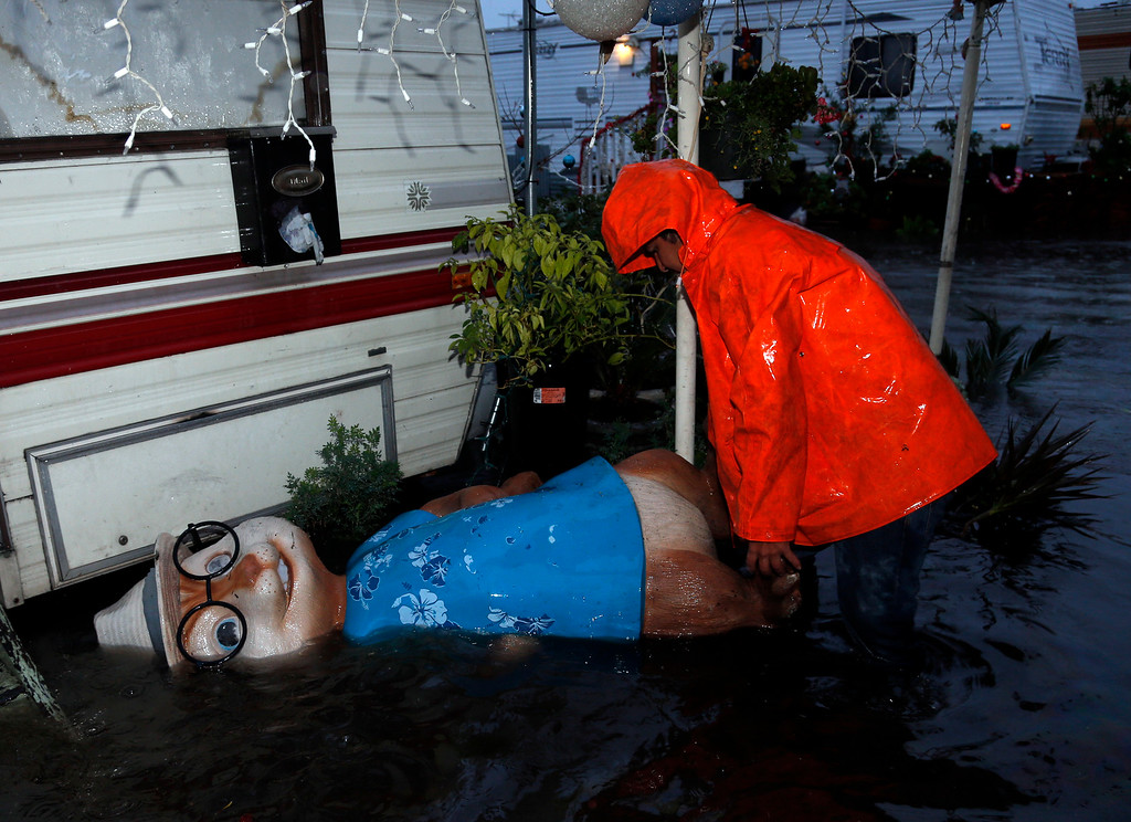 . Juan Guzman checks on a toppled Christmas decoration at outside his home at the flooded Le Mar Trailer Park in Redwood City, Calif., Thursday evening, Dec. 11, 2014. (Karl Mondon/Bay Area News Group)