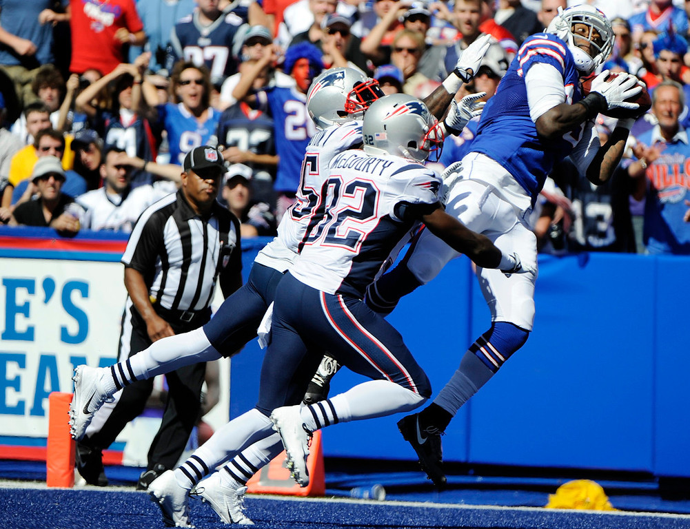 . Buffalo Bills wide receiver Steve Johnson (13) catches a pass for a touchdown over New England Patriots free safety Devin McCourty (32) and Kyle Arrington during the second half of an NFL football game on Sunday, Aug. 8, 2013, in Orchard Park. (AP Photo/Gary Wiepert)