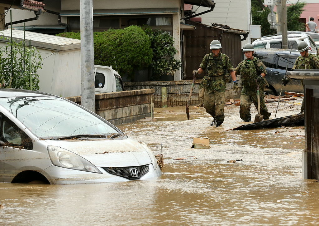 . Members of Ground Self-Defense doing rescue work in an area damaged by a landslide caused by torrential rain at the site of a landslide in a residential area on August 20, 2014 in Hiroshima, Japan.  (Photo by Buddhika Weerasinghe/Getty Images)