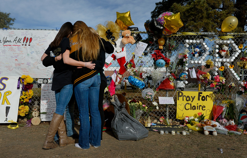 . A group of students embrace at the tribute area outside Arapahoe High School in Centennial, CO December 19, 2013. Seniors and Juniors will return to the school for two hour periods Thursday, Sophomores and Freshmen will return on Friday. (Photo By Craig F. Walker / The Denver Post)