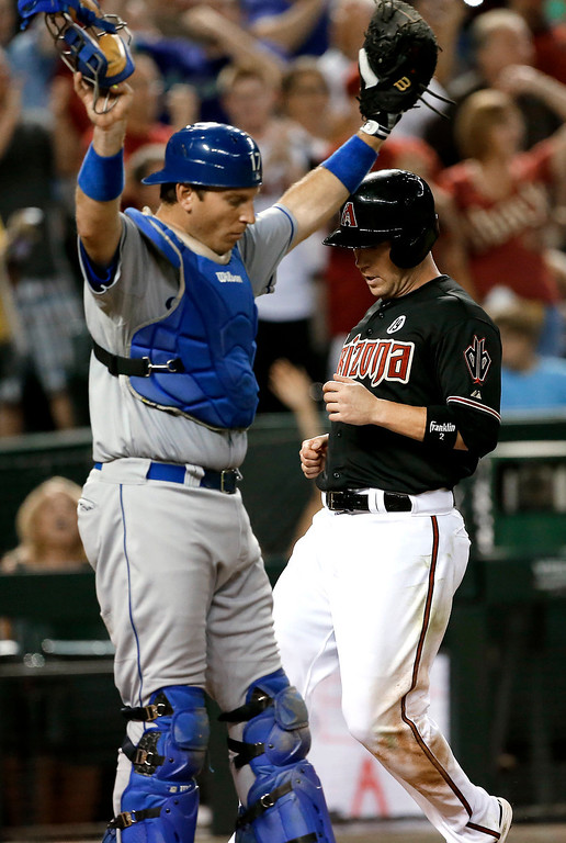 . Arizona Diamondbacks\' Aaron Hill scores on a double by Paul Goldschmidt as Los Angeles Dodgers catcher A.J. Ellis stands at the plate during the fifth inning of a baseball game, Wednesday, July 10, 2013, in Phoenix. (AP Photo/Matt York)