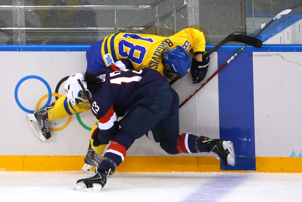 . SOCHI, RUSSIA - FEBRUARY 17:  Julie Chu #13 of the United States collides with Anna Borgqvist #18 of Sweden in the first period during the Women\'s Ice Hockey Playoffs Semifinal game on day ten of the Sochi 2014 Winter Olympics at Shayba Arena on February 17, 2014 in Sochi, Russia.  (Photo by Doug Pensinger/Getty Images)