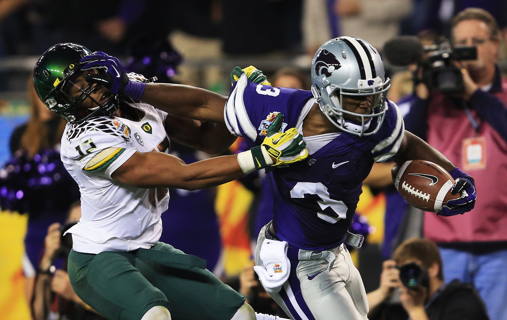 Description of . Ifo Ekpre-Olomu #14 of the Oregon Ducks tries to tackle Chris Harper #3 of the Kansas State Wildcats during the Tostitos Fiesta Bowl at University of Phoenix Stadium on January 3, 2013 in Glendale, Arizona.  (Photo by Doug Pensinger/Getty Images)