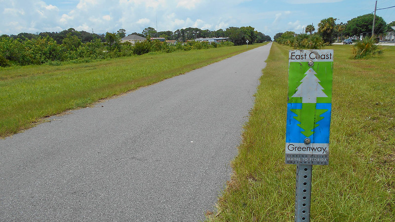 East Coast Greenway sign with bike path beyond