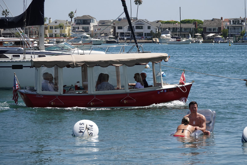 """Relaxing in the water, as a """"Duffy"""" boat sails by on a summer afternoon."""