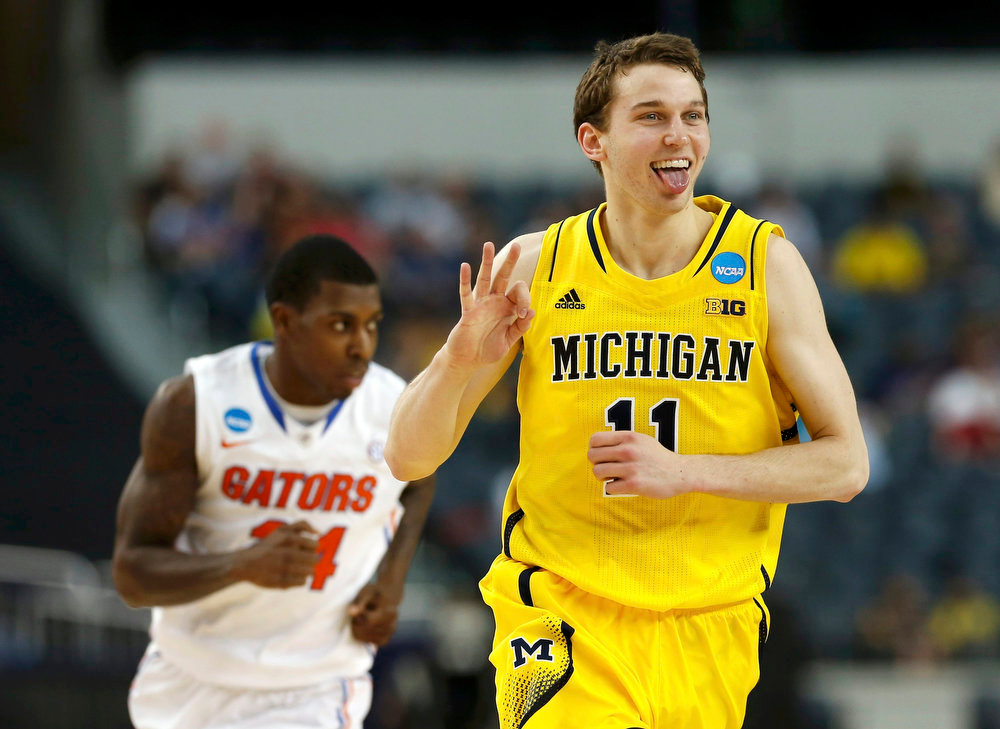 . Michigan Wolverines guard Nik Stauskas (R) celebrates hitting a three point shot over the Florida Gators in their South Regional NCAA men\'s basketball game in Arlington, Texas March 31, 2013. REUTERS/Jim Young