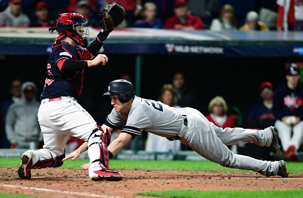 . New York Yankees\' Todd Frazier slides safely into home plate as Cleveland Indians catcher Roberto Perez waits for the ball during the ninth inning of Game 5 of a baseball American League Division Series, Wednesday, Oct. 11, 2017, in Cleveland. (AP Photo/David Dermer)