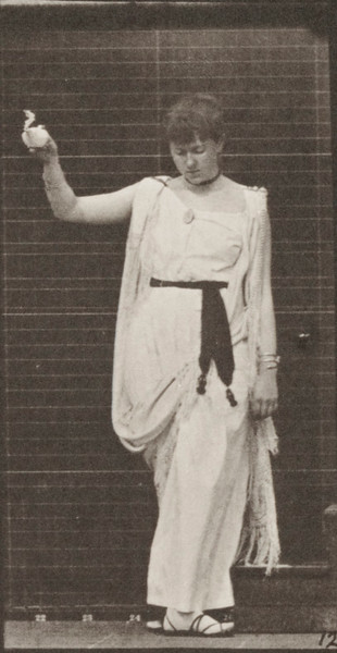 Woman descending stairs and turning holding a lamp in right hand