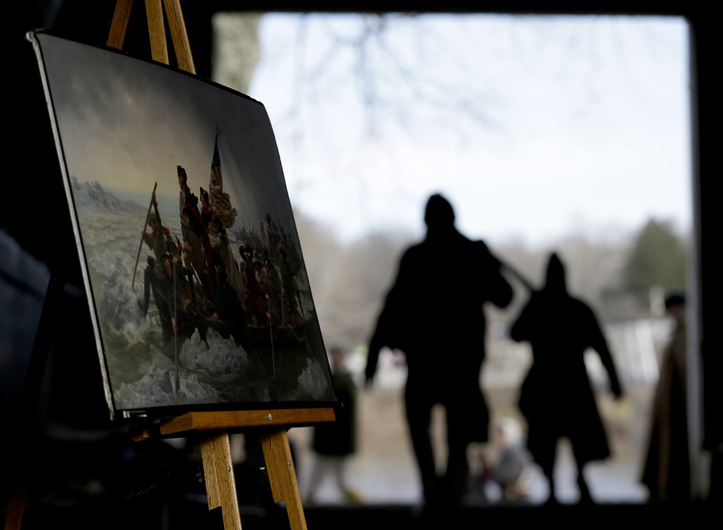 . A print of a painting depicting Gen. George Washington\'s troops crossing the Delaware River in 1776 is displayed in a boathouse as actors carry oars during the 61st annual re-enactment of Washington\'s daring Christmas 1776 crossing of the river, the trek that turned the tide of the Revolutionary War, in Washington Crossing, N.J. During the crossing 237 years ago, boats ferried 2,400 soldiers, 200 horses and 18 cannons across the river, and the troops marched eight miles downriver before battling Hessian mercenaries in the streets of Trenton. (AP Photo/Julio Cortez)