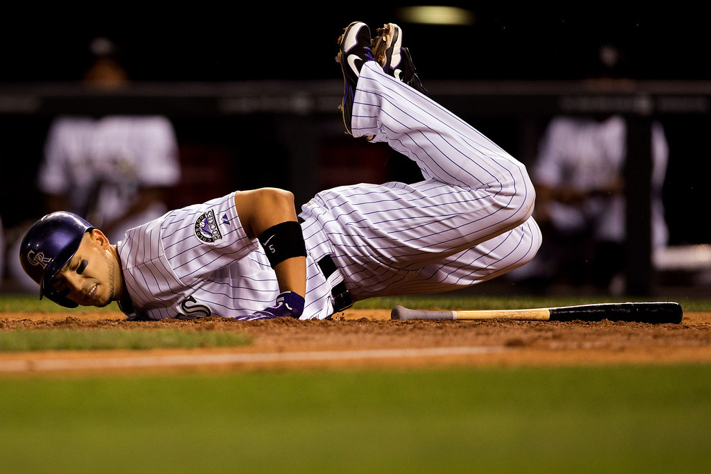 . DENVER, CO - JULY 19:  Carlos Gonzalez #5 of the Colorado Rockies lies near home plate after tripping on a bunt attempt in the seventh inning against the Chicago Cubs at Coors Field on July 19, 2013 in Denver, Colorado.  Gonzales went on to strike out in the at-bat. (Photo by Justin Edmonds/Getty Images)