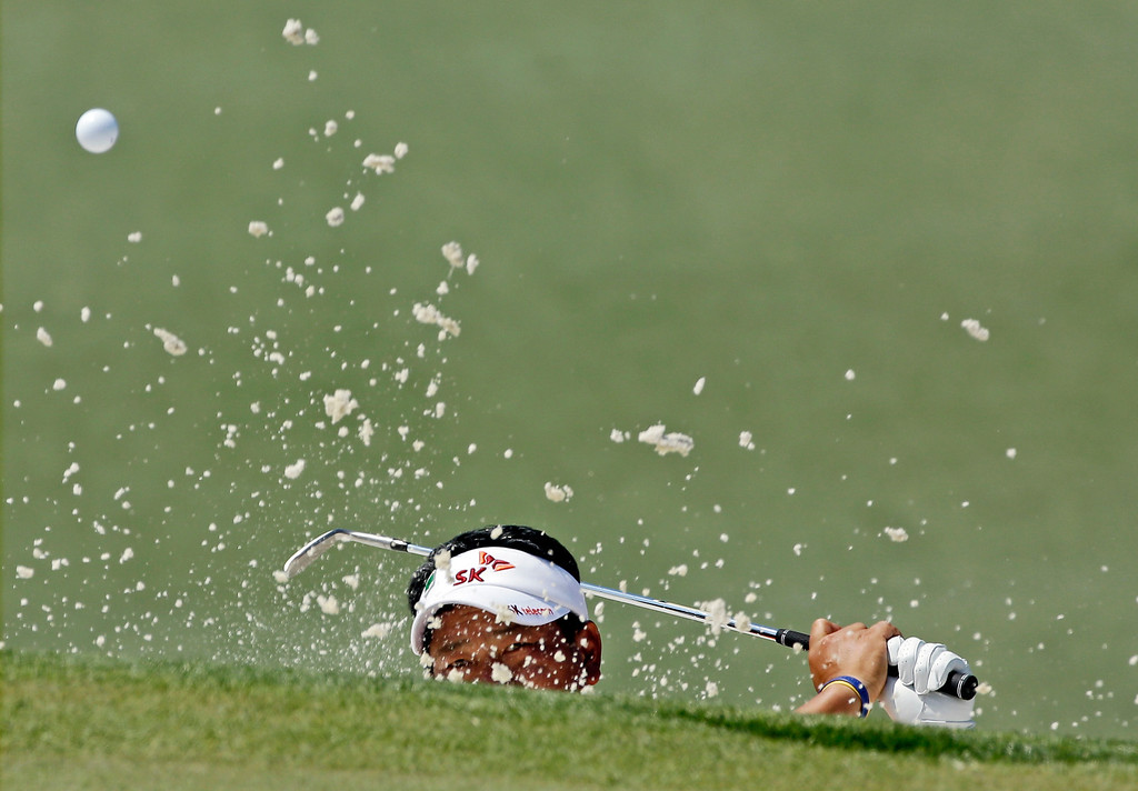 . K.J. Choi, of Korea, hits out of a bunker on the seventh hole during the third round of the Masters golf tournament Saturday, April 12, 2014, in Augusta, Ga. (AP Photo/David J. Phillip)
