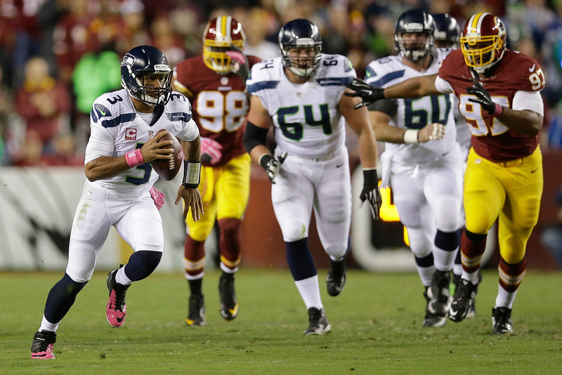 . Seattle Seahawks quarterback Russell Wilson (3) scrambles with the ball during the first half of an NFL football game against the Seattle Seahawks in Landover, Md., Monday, Oct. 6, 2014. (AP Photo/Patrick Semansky)