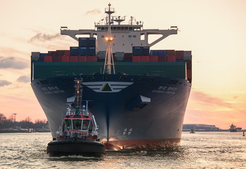 Bugsier 5 vor Containerschiff bei dem Dämmerung