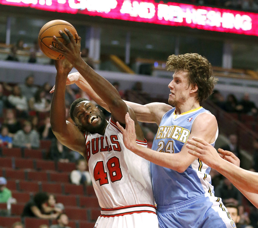 . Denver Nuggets forward Jan Vesely (24) fouls Chicago Bulls center Nazr Mohammed (48) during the second half of an NBA basketball game Friday, Feb. 21, 2014, in Chicago. The Bulls won 117-89. (AP Photo/Charles Rex Arbogast)