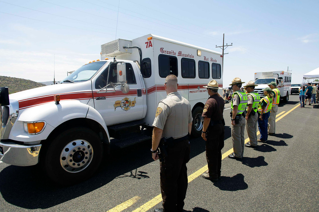 . Arizona Department of Public Safety Officers and Yavapai County Sheriff Officers salute the fire vehicles used by the 19 firefighters who perished battling a fast-moving wildfire in Peeples Valley, Arizona July 3, 2013. Weary crews on Tuesday looked for a break in the weather to gain ground against a fierce Arizona wildfire that has already killed 19 of their fellow firefighters in the worst wildland fire tragedy in 80 years. Fire managers say the so-called Yarnell Hill fire, which has already charred nearly 8,400 acres (3,400 hectares) of tinder-dry chaparral and grasslands northwest of Phoenix, was zero percent contained as darkness fell on Monday evening. REUTERS/Joshua Lott