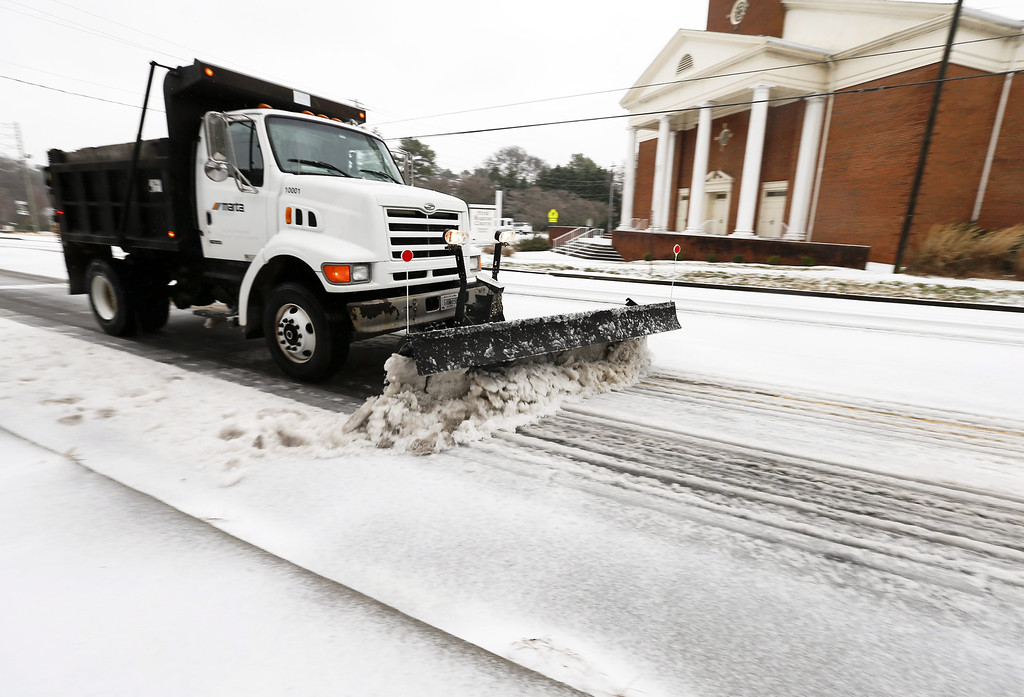. A snow plow operated by the Metropolitan Atlanta Rapid Transit Authority clears a path on a snow and ice covered Covington Highway during a severe winter storm in Avondale Estates, Georgia, USA, 12 February 2014. Ice and snow in the metro Atlanta area and north Georgia is expected to make travel treacherous and cut electricity to thousands of customers.  EPA/ERIK S. LESSER