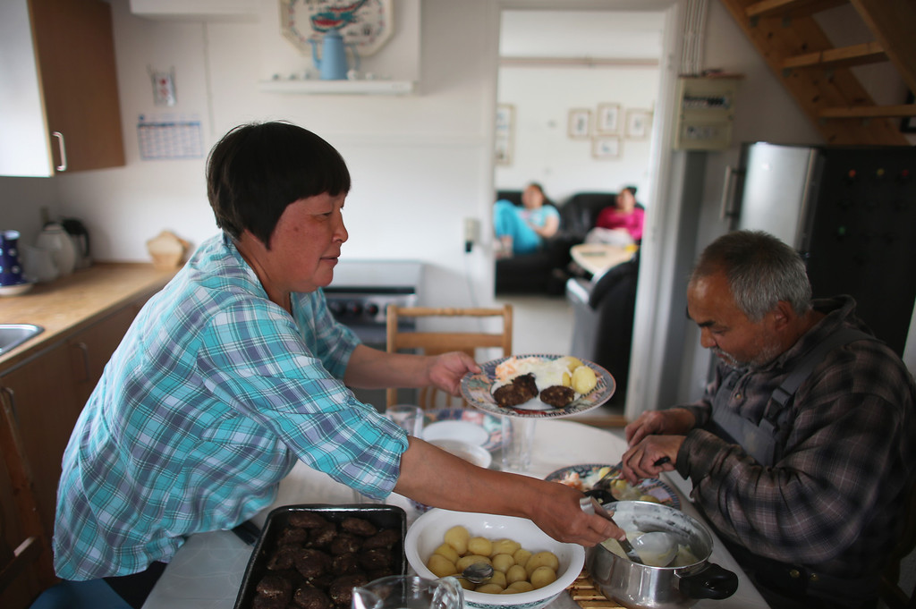 . Potato farmers Arnaq Egede (L) and Ferdinan Egede eat lunch together at the house on the family\'s farm on July 31, 2013 in Qaqortoq, Greenland.   (Photo by Joe Raedle/Getty Images)