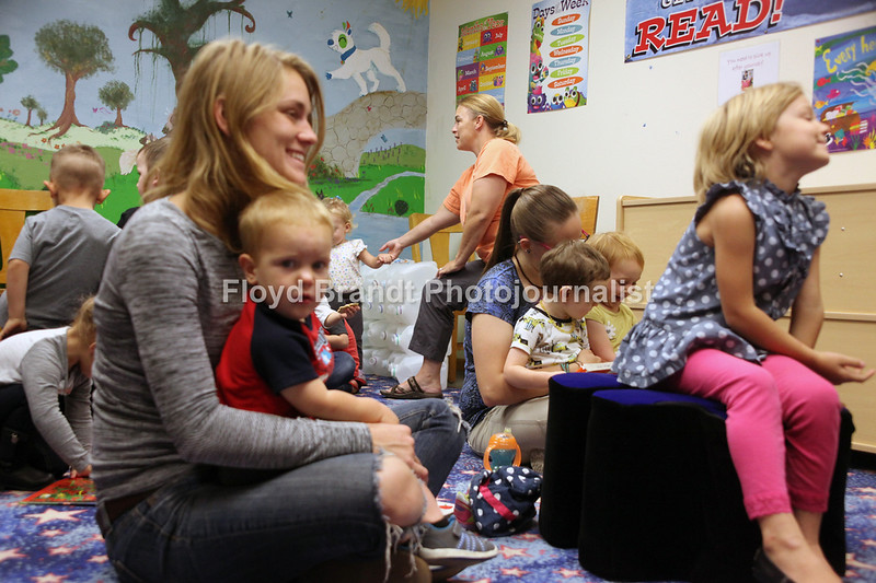 Havre Daily News/Floyd Brandt  Michael Pension with nephew Jake Kanutson in her lap and daughter 5 year old  Ambros Reams (right) listens to Ashley Martin read a story during Story Time at Havre Hill County Library Wednesday.