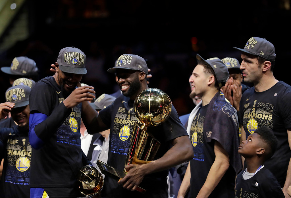 . Golden State Warriors\' Draymond Green celebrates after the Warriors defeated the Cleveland Cavaliers 108-85 in Game 4 of basketball\'s NBA Finals to win the NBA championship, Friday, June 8, 2018, in Cleveland. Next to Green are Kevin Durant, left, and Klay Thompson. (AP Photo/Tony Dejak)