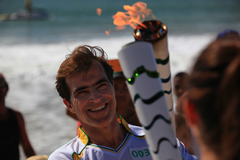 Carlos Burle Passing Olympic Torch.jpg