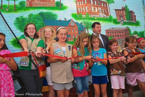 Emily Ekross (left) help her Girl Scout volunteers in cutting the ceremonial ribbon during the dedication of the new history mural at the 4 Corners in Baldwinsville, New York on Wednesday, August 7, 2013. Baldwinsville Mayor Joseph Saraceni (in back) counted down the cutting.